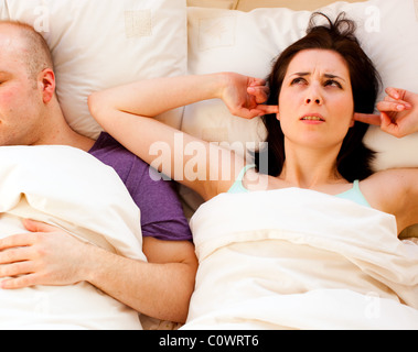 Woman fed up of partner snoring - Stock Photo