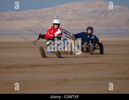 Kite buggyers racing on Westward Ho! Beach, North Devon, UK - Stock Photo