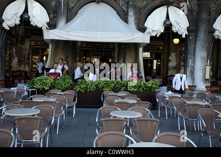 A band play at one of the restaurants on St Marks Square Piazza in an attempt to win business. Empty tables in the - Stock Photo