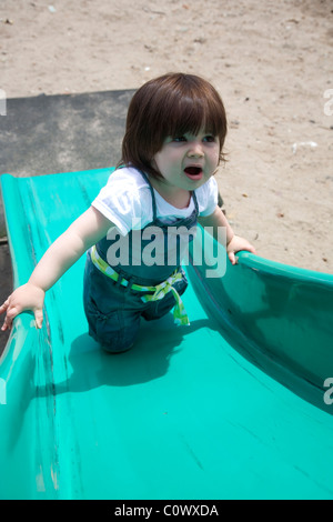 Young child climbing slide in playground - Stock Photo