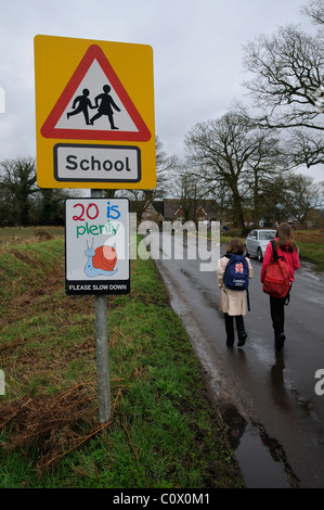 Schoolchildren walking to school along a country lane without pavement or walkway Hampshire England UK - Stock Photo