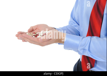 Red and white tablets in male hands - Stock Photo