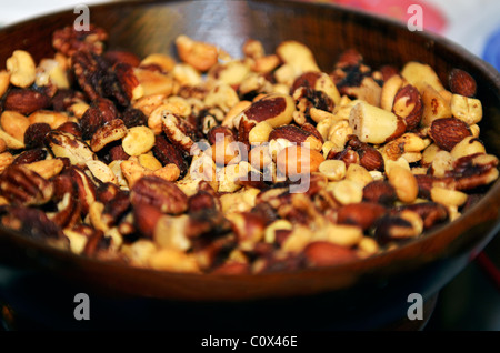 A wooden bowl filled with roasted, salted mixed nuts. Closeup. - Stock Photo