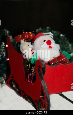 A Christmas decoration of Santa Claus in a wooden sleigh, with gifts. - Stock Photo