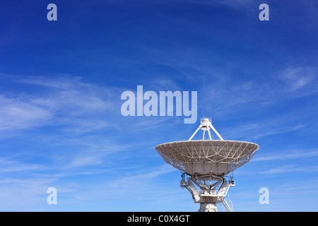 A radio telescope dish in the Very Large Array against blue New Mexico sky. - Stock Photo