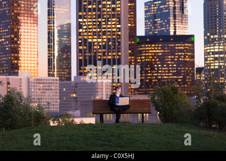 Male sitting on park bench working on laptop computer with Los Angeles city skyline in background at dusk, sunset - Stock Photo