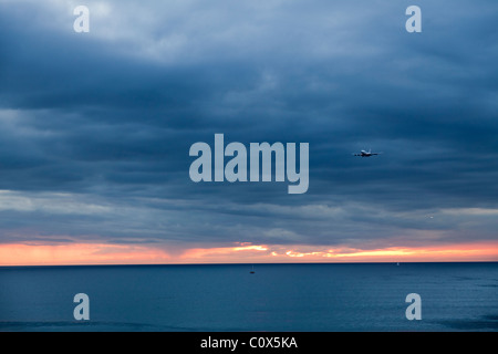 Aircraft passenger jet landing over ocean against cloudy dramatic sky. Dockweiler Beach in Los Angeles, California. - Stock Photo