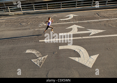 Female runner running on urban city street bridge, overpass with directional arrows painted on pavement - Stock Photo