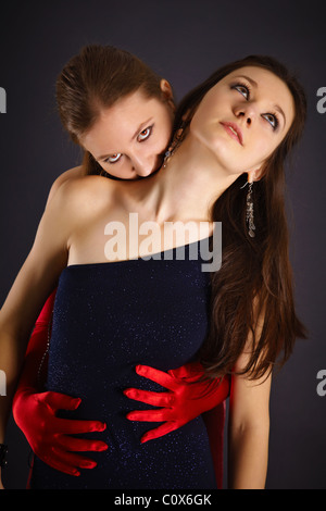 Two young girls portrayed the vampire and his sacrifice on dark background - Stock Photo