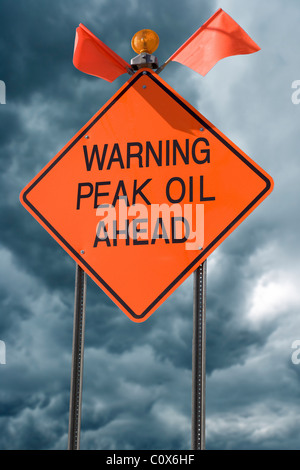 An orange highway safety sign with the words 'Warning Peak Oil Ahead' on it. - Stock Photo
