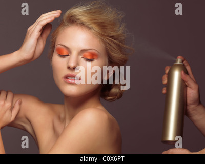 Hairstylist spraying hair product on beautiful young woman's blond hair - Stock Photo