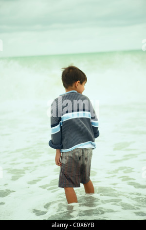 Eight year old boy in the sea on an overcast autumnal day, Napier, New Zealand - Stock Photo