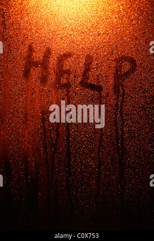 Help - finger tip writing on window with condensation. - Stock Photo
