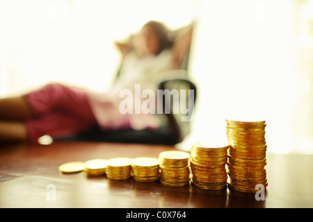 Investing in gold. Girl with stacked chocolate gold coins. - Stock Photo
