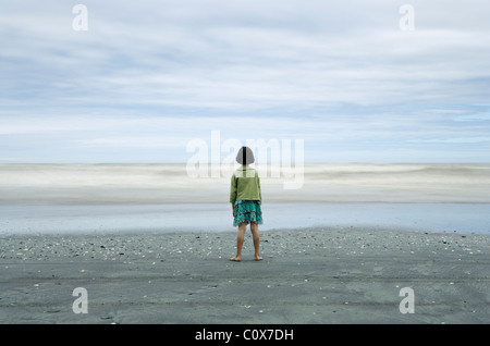 Girl in sharp focus looks at sea, with waves blurred by long exposure; black volcanic sand, Manawatu, New Zealand. - Stock Photo