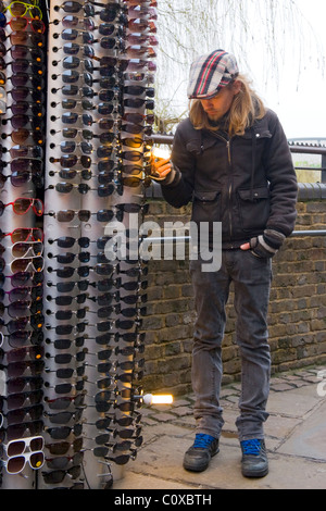 Camden Town or Lock or Horses Market , London , sunglasses stall holder young man or boy in peaked cap with long - Stock Photo