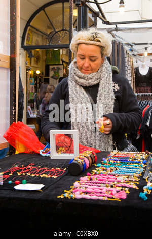Camden Town or Lock or Market , London , pretty young lady or girl arranges necklaces & bracelets on her stall or - Stock Photo