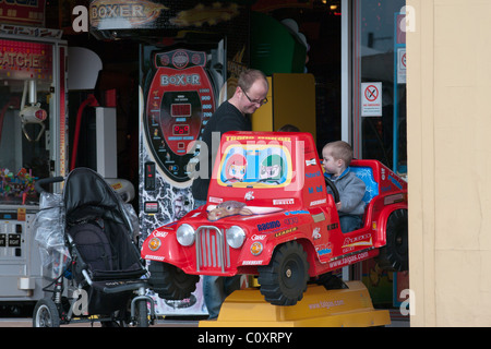 Man with a Boy Riding On A Childs Ride At Amusement Arcade - Stock Photo