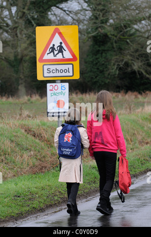 Schoolchildren walking to school along a country lane with no pavement Hampshire England UK - Stock Photo