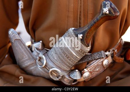 A man wears an ornate silver Khanjar dagger in his belt in Oman. - Stock Photo