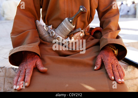 The age worn hands of a man at the cattle market in Nizwa, Oman. - Stock Photo