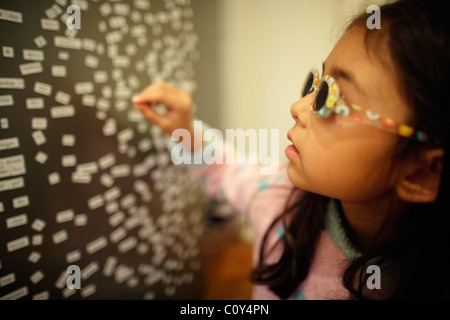 Girl wears sunglasses and plays with magnetic fridge words - Stock Photo