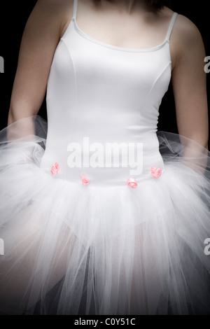 Portrait of teenage ballerina wearing a white tutu with small pink flowers. - Stock Photo