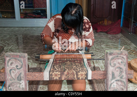 Woman doing traditional ikat weaving in the aboriginal Aga village of Tenganan in eastern Bali - Stock Photo