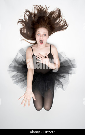 A teenager wearing a black tutu jumps in the air. - Stock Photo