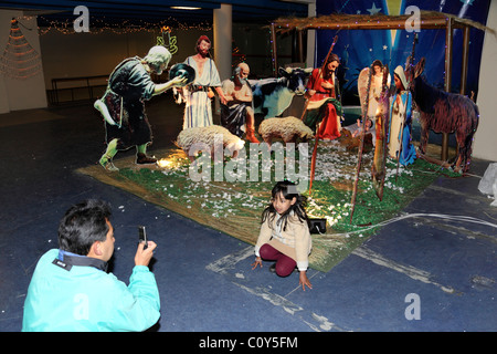 Man taking photo of his daughter in front of life size cardboard cut out nativity scene , La Paz , Bolivia - Stock Photo