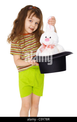 A child gets a rabbit out of a hat like a magician isolated on white background - Stock Photo