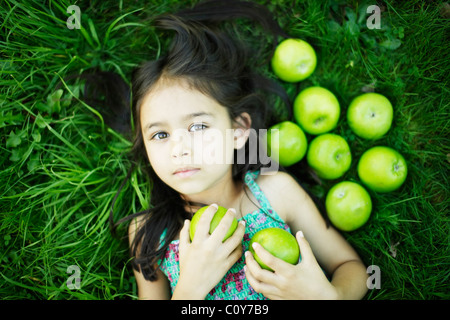 Six year old girl lies on grass with green apples - Stock Photo