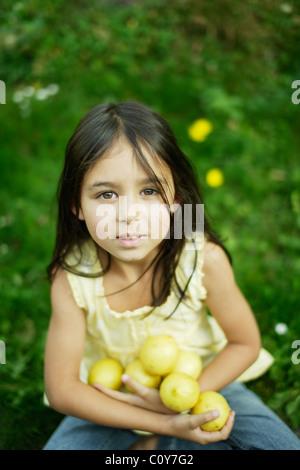 Six year old girl sits on lawn and holds lemons - Stock Photo