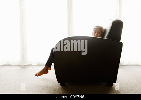Six year old girl sits in art deco style armchair beside window. - Stock Photo
