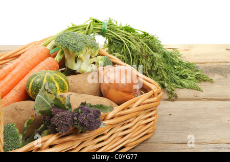 Fresh vegetables in a wicker basket on a wooden bench - Stock Photo