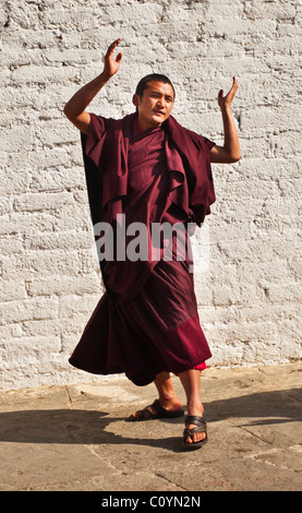 Bhutanese monk(s) practicing dance steps prior to appearing in a major religious festival. - Stock Photo