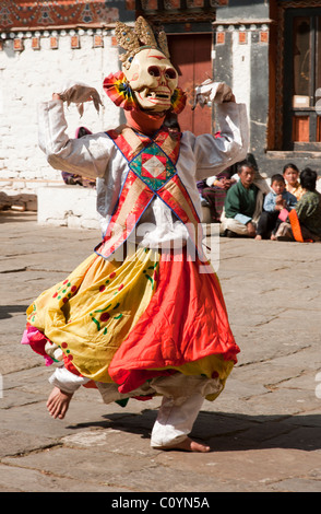 Festival dancer representing the warding off of evil dances in the main square of the Trongsa Dzong during a festival - Stock Photo