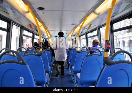 Inside London double decker bus top deck interior back view of passengers top deck one standing most sitting down - Stock Photo