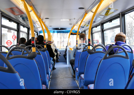 Inside London double decker bus top deck interior back view of passengers on top deck sitting down with view of - Stock Photo