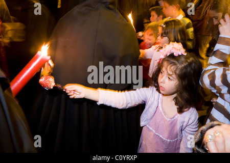 Church member penitent processing in Semana Santa Easter Holy week procession gives candle wax to child / girl, - Stock Photo