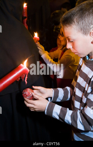 Church member penitent processing in Semana Santa Easter Holy week procession gives candle wax to child / boy, in - Stock Photo