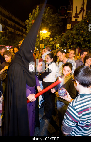 Church member penitent processing in Semana Santa Easter Holy week procession gives candle wax to child / children - Stock Photo