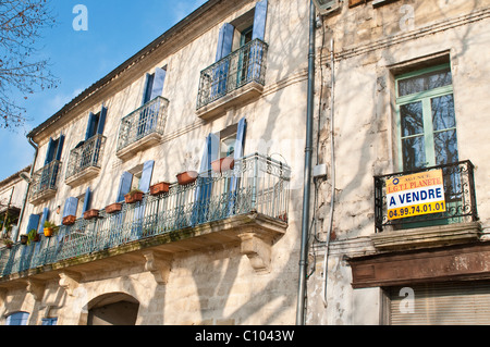 Old house with Sale sign, Sommieres, Gard, Languedoc, France - Stock Photo