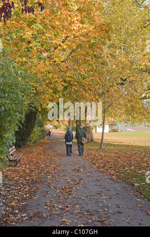 A couple walk along a path on The Stray, Harrogate,  in autumn. - Stock Photo