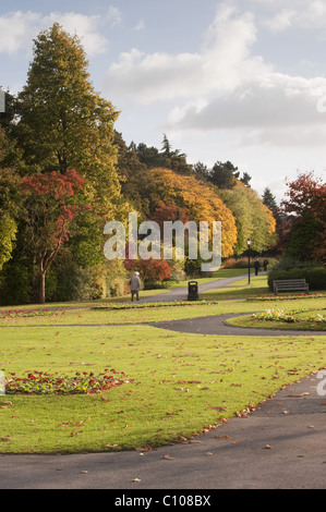 Beautiful urban landscaped park in autumn with bright colourful leaves on trees, & people relaxing - Valley Gardens, - Stock Photo