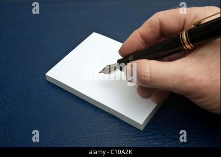 A male hand holding a Mont Blanc Meisterstuck 149 fountain pen about to write on a white writing pad - Stock Photo