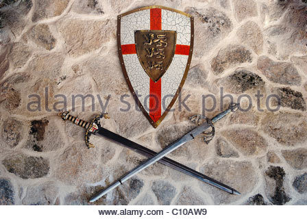 Middle age metallic shield and two swords on a wall - Stock Photo