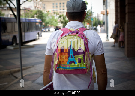 Rear view of man wearing a child's backpack - Stock Photo
