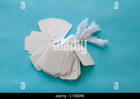 white blank price tags with string on blue surface - Stock Photo