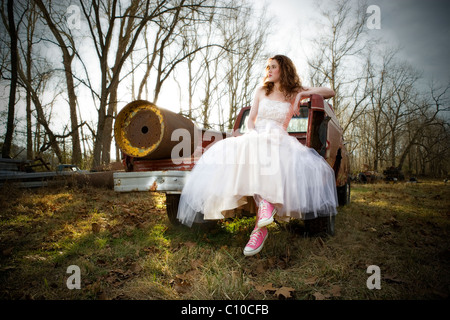 A young teenage girl wearing a white prom dress sits on the back of an old rusted red truck in a field in Virginia. - Stock Photo